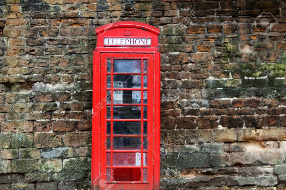 10087614-The-British-red-phone-booth-on-old-wall-Stock-Photo
