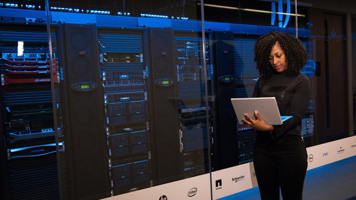 Woman using laptop in front of servers