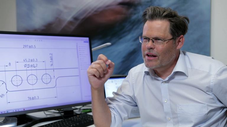 Dr. Klügl erklärt die Konstruktion der Faceshields. Bequem und stabil.