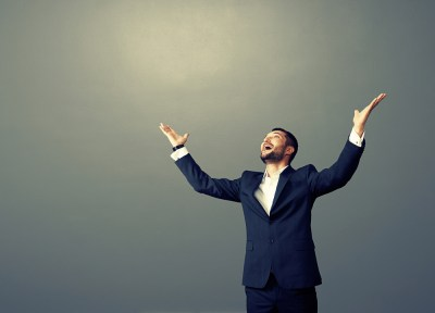 laughing businessman with arms up