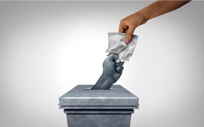 democracy - vote cast by dropping a ballot into a ballotbox