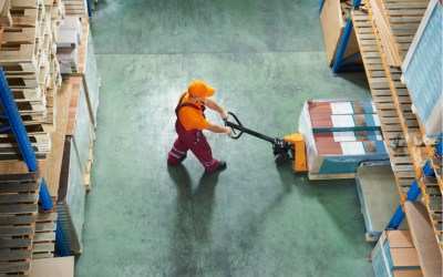 worker with fork pallet truck stacker in warehouse loading panels