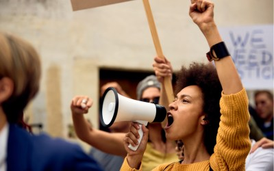 young activist woman marches in the street - democracy