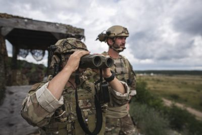 concept - us military looking through binoculars at a future where viewing climate as a national security threat increases militarism - biden administration