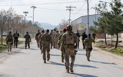 Rear View Of Army Soldiers Walking On Road In City