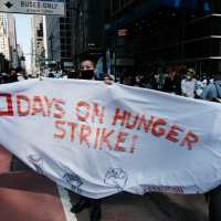 protesters holding a sign that says hunger strike