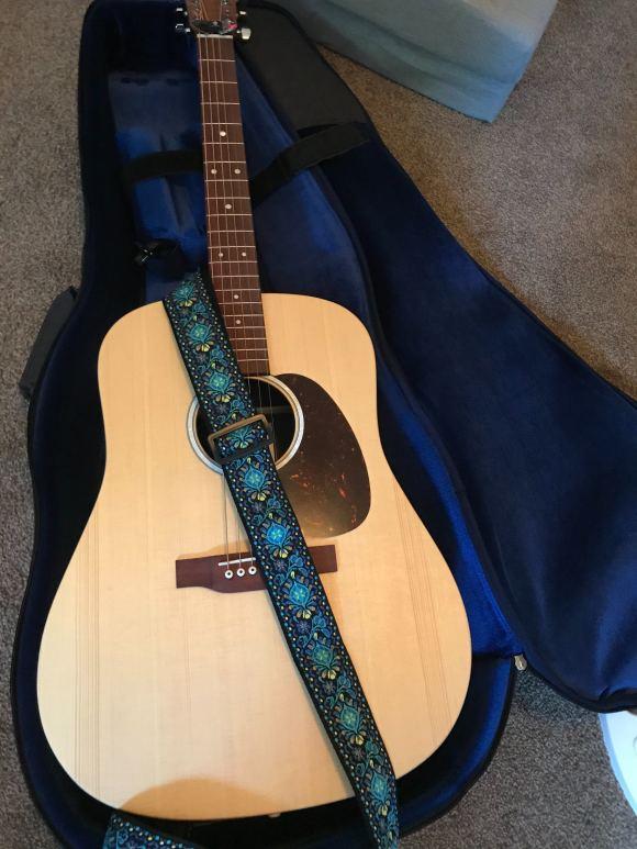 A Martin D-X2E Acoustic Electric Guitar with a blue hippie strap.