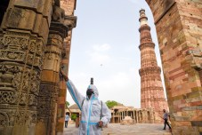 New Delhi, June 15 (ANI): A worker sprays sanitizer inside Qutub Minar premises as the state government allows the re-opening of monuments, in New Delhi on Tuesday. (ANI Photo)