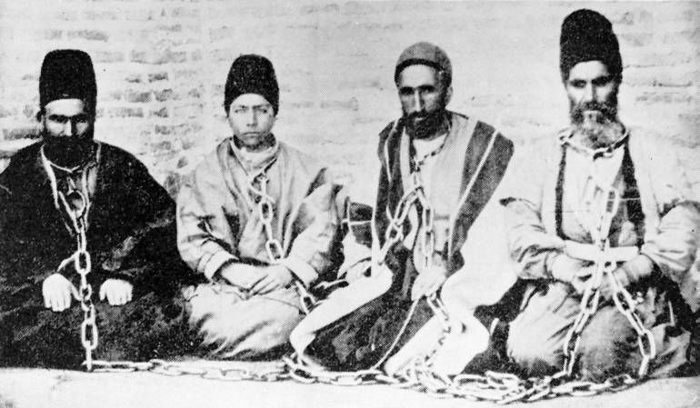 A Bahá'í father and son (at left) in chains after being arrested with fellow Bahá'ís, in a photograph taken around 1896. Both were subsequently executed.