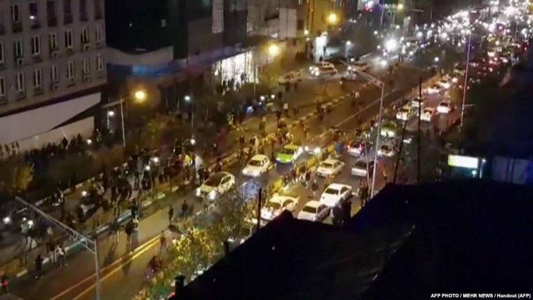 (1/1)Iran -- An image grab taken from a handout video released by Iran's Mehr News agency reportedly shows a group of men walking down a street in Tehran on December 30, 2017. Ten people died overnight in fresh unrest in Iran, local media reported on January 1