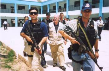 Kerik walks amidst a phalanx of bodyguards during visit to the Police Academy in Baghdad, July 2003.