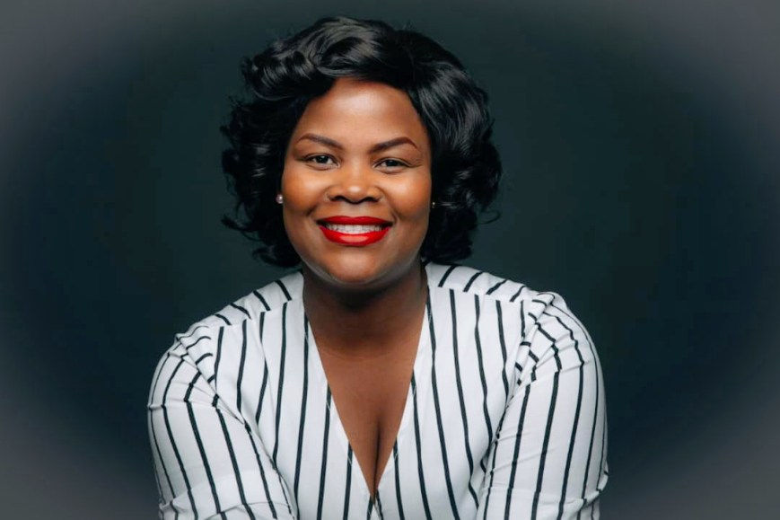 Cathy Sibanda, chemise blanche rayée de noir, un large sourire