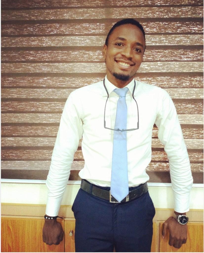 Martin Beck Nworah, debout, sourire, chemise blanche, cravate bleue claire, lunettes au cou