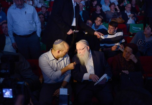 Naftali Bennett (à gauche), député de la coalition Yamina du parlement israélien, s'entretient avec le rabbin Haim Druckman. Ils sont au milieu d'une foule de croyants.