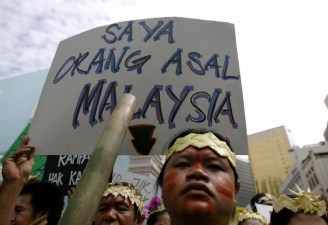 An indigenous Malaysian holds placard during demonstration in Kuala Lumpur