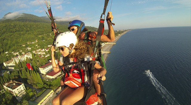 Couple paragliding over some mountains