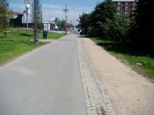 A greenway in Copenhagen with footpath and two-way cycle path separated by a stone drainage channel