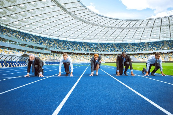 Photo of confident multi ethnic business people lined up getting ready for race on modern sport track. Stadium as a background