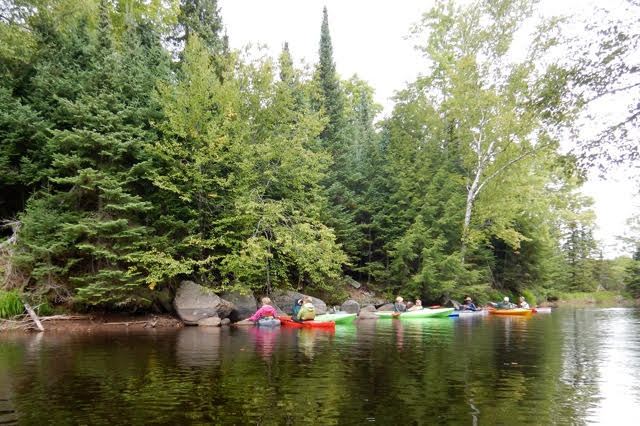 Kayaks on a lake near forested shoreline