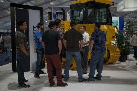 IronDirect Vice President Tom Hlawek speaks to visitors about the Shantui dozers on display at the booth.