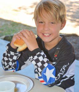 Child eating hot dog.
