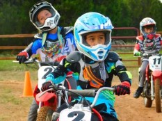 child leaning to ride dirt bike at motocross summer camp