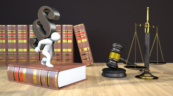 Manikin with paragraph on the wooden table with gavel, balance and law books. 3d illustration.
