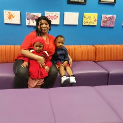 Regina Malone with her children, Kevin and Alexy, enjoy the new seating in the food pantry waiting room
