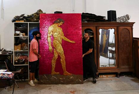 Toledo (right) moves with his assistant a biblical work of art depicting Adam.  The work is part of a future corona exhibition.