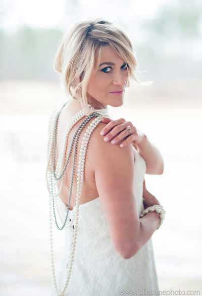 Bride looking over her shoulder wearing long layered pearl necklaces in back