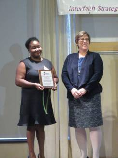 Ms. Grace Lubwama, YWCA executive director and leader of Cradle Kalamazoo, receives an ISAAC Community Builder Award from Wesley Foundation director Rev. Lisa Batten for sponsorship and partnership with ISAAC.