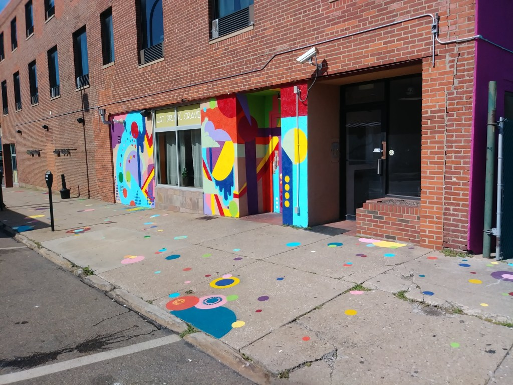 Painting on the walls extends to the sidewalk giving a playful sense of happiness. Some patterns are spray painted atop the colored dots.