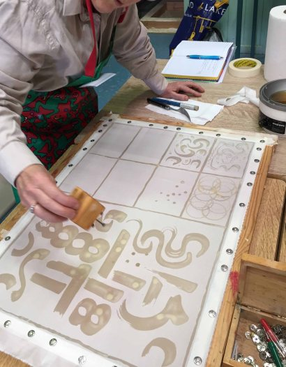 Making a wax sampler. This student is using a wooden block set with nails to make dots
