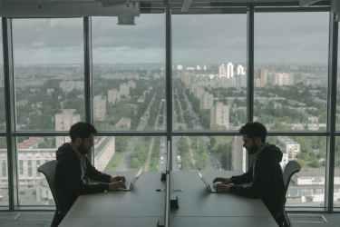 man in black jacket sitting beside window