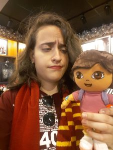 a girl looking at Dora the Explorer, wearing a Gryffindor scarf