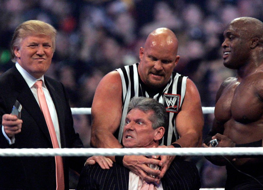 """WWE Chairman Vince McMahon, center, held by """"Stone Cold"""" Steve Austin, prepares to have his hair cut off by Donald Trump"""