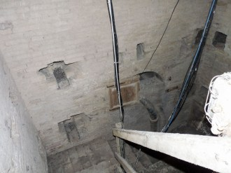 Interno torre civica con tubature del vecchio acquedotto del 1895 e vano del deposito dell'acqua.