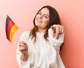 Girl holding German flag pointing out how to study in Germany for free