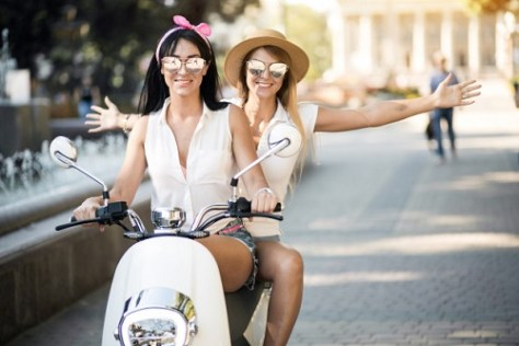 Two girls traveling on a scooter