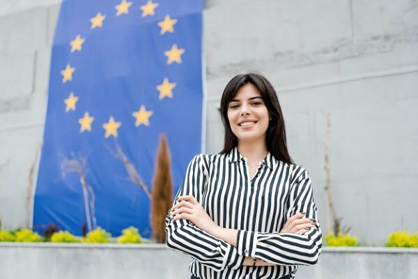 Girl standing in front of the European Union flag and talking about the best countries to study in Europe