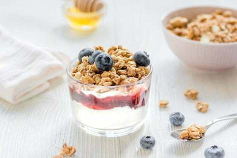 Fitness breakfast with muesli, honey and berries on white table