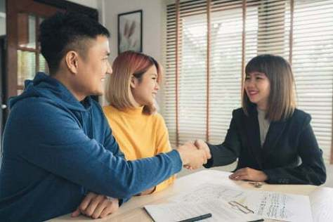 Happy young Asian couple and realtor agent. Cheerful young man s
