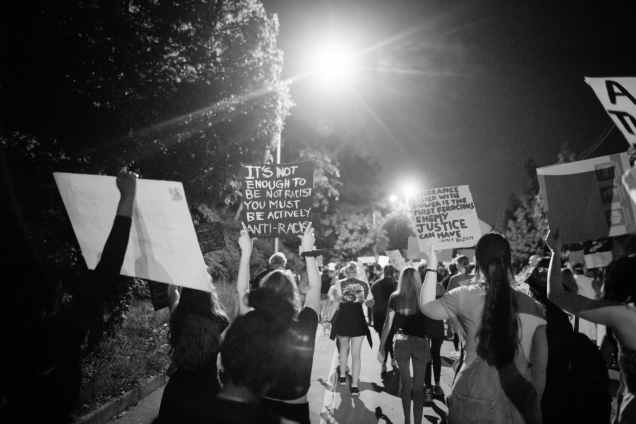 group of people protesting on street at night