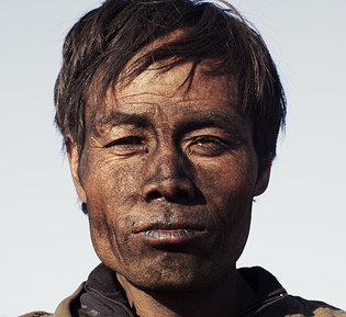 man's face covered in coal