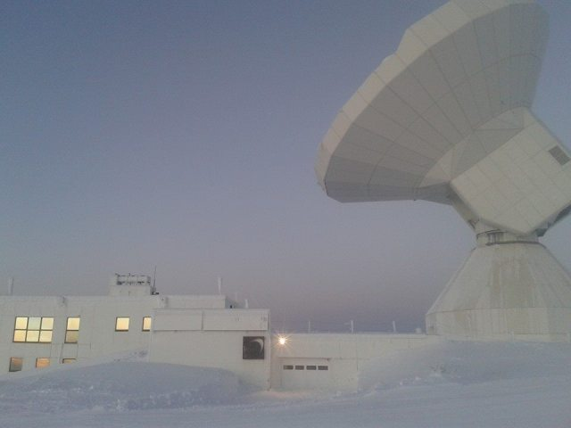 telescope and astronomy building surrounded by snow