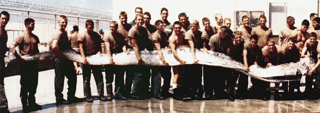 lots of men holding a giant Oarfish