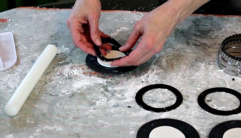 attaching black fondant ring onto fidget spinner cake