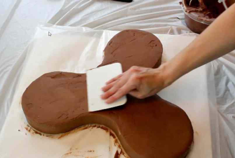 covering the fidget spinner cake in chocolate buttercream