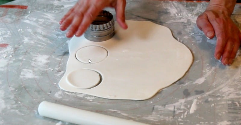 cutting out white fondant circles for fidget spinner cake