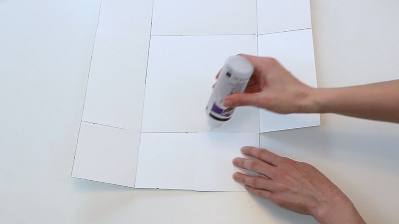 adding glue to folded flaps of the poster board